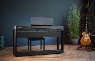 Kawai ES920 digital piano sitting on small stage with guitar and plant