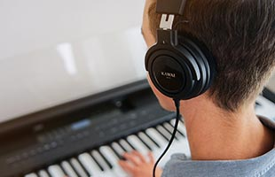 over-the-shoulder view of musician playing Kawai ES920 digital piano while wearing headphones