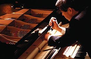 close-up image of piano technician making adjustments to Kawai grand piano