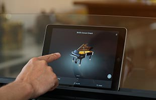 close-up image of tablet computer on Kawai ES920 digital piano music rest with hand touching screen