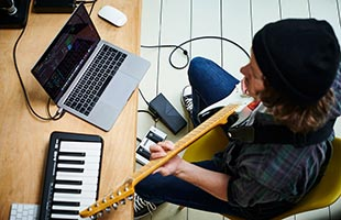 view from above of musician playing guitar with Boss EV-1-WL while sitting in front of project studio desk with keyboard controller and laptop computer running music recording software