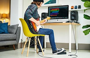 musician playing guitar with Boss EV-1-WL while sitting in front of project studio desk with desktop computer running music recording software