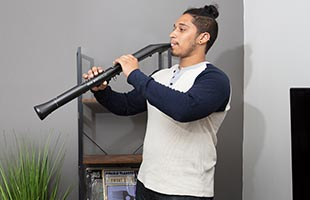 musician playing Akai Professional EWI Solo wirelessly in living room