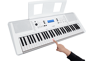 3/4 view Yamaha EZ-300 showing top, front and left side with superimposed disembodies hand using index finger to play lit EZ-200 key