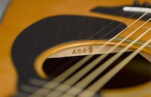 detail image of Yamaha Red Label acoustic guitar soundhole showing A.R.E. logo on underside bracing