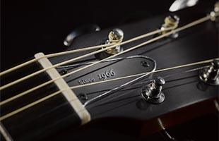 detail image of Yamaha Red Label acoustic guitar headstock showing bone nut