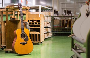 Yamaha Red Label acoustic guitar standing on floor in Yamaha guitar factory
