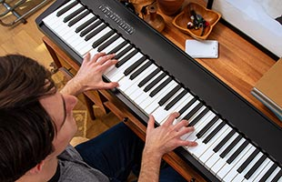 overhead view of musician playing Roland FP-30X on studio desk