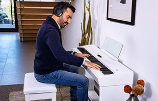 musician wearing headphones playing Roland FP-60x in living room