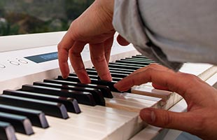close-up image of musician's fingers playing PHA-50 Hybrid keyboard on Roland FP-90X