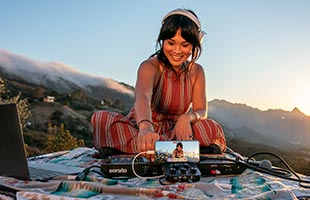 musician wearing headphones and playing keyboard recording performance with Roland Go:Mixer Pro-X and smartphone in outdoor hilltop setting