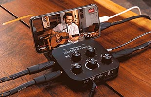 close-up top view of Roland Go:Mixer Pro-X and smartphone on table with several audio and video cables connected and onscreen image of musician performing with acoustic guitar and microphone
