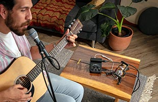 close-up side view of musician performing in living room with acoustic guitar, microphone and Roland Go:Mixer Pro-X