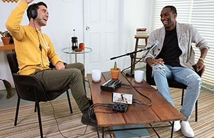 two podcast hosts in living room recording podcast with Roland Go:Mixer Pro-X and microphone