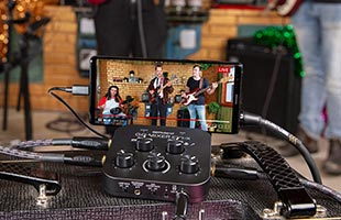 close-up view of Roland Go:Mixer Pro-X and smartphone on table with onscreen image of band performing in background