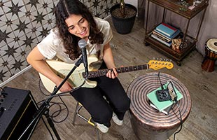 overhead view of musician performing in living room with guitar, microphone and Roland Go:Mixer Pro-X