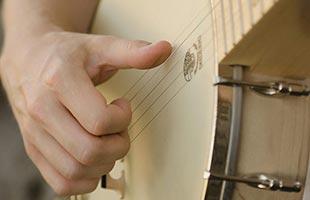 detail image of banjo player's hand playing Deering Goodtime Americana
