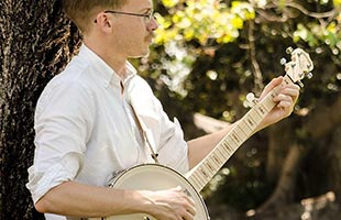 close-up image of banjo player playing Deering Goodtime Americana leaning against tree