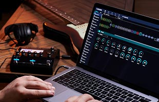 close-up point-of-view image of musician's hands on laptop computer running Boss Tone Studio software with Boss GT-1000CORE, guitar and headphones in background