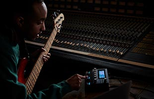 bass player playing bass guitar in studio setting with Boss GT-1000