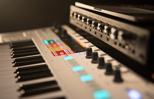 side view of Arturia KeyStep Pro in front of audio interface and laptop computer