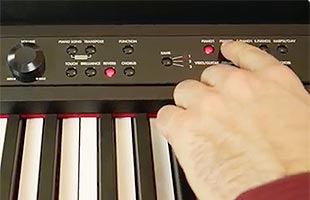 close-up view of piano player's fingers using control panel on Korg LP-380U to choose sound