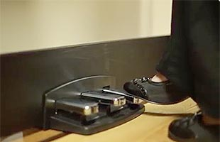 close-up side image of piano player's foot pressing sustain pedal on Korg LP-380U