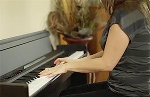 close-up side view of piano player playing Korg LP-380U in living room