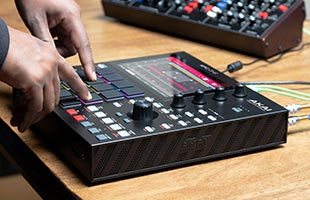 close-up side view of musician's hands manipulating controls on Akai Professional MPC One with connected synthesizer module in background