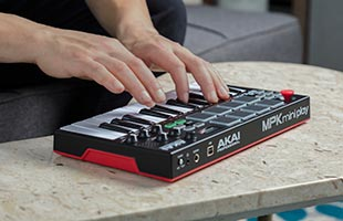 close-up image of musician's hands playing keys on Akai Professional MPK Mini Play