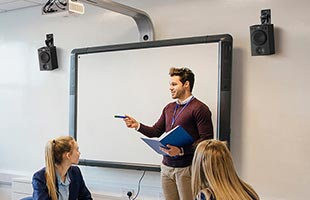 instruction and students in classroom equipped with wall-mounted Yamaha MSP3A speakers