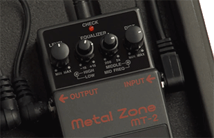 close-up top view of Boss MT-2 Metal Zone guitar distortion effects pedal on pedal board