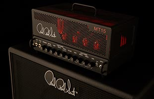 PRS MT15 sitting on amplifier cabinet lit to appear as if vacuum tubes are glowing red