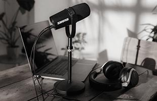 Shure MV7 on table with laptop computer and headphones in background