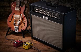 Boss Nextone Special guitar amplifier next to guitar on stand with effects pedals on floor