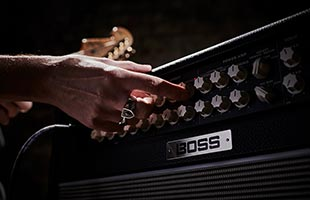 close-up image of Boss Nextone Special guitar amplifier front panel with guitarist's hand reaching to adjust controls
