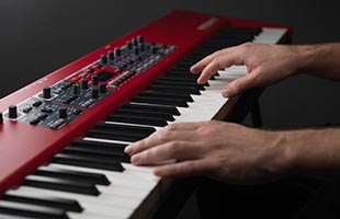 close-up view from side of musician's hands playing Nord Piano 5