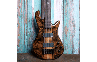 close-up top view of Spector NS Ethos 5 resting against painted wood wall showing body and portion of fretboard