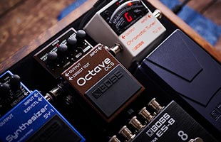 Boss OC-5 on guitar pedalboard surrounded by tuner, expression pedal and other stompboxes