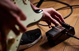 close-up image of guitarist playing with right hand while operating Boss OC-5 on floor with left hand