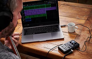 over-the-shoulder view of sitting musician wearing headphones and playing guitar with Boss Pocket GT sitting on table alongside laptop computer running recording software