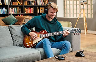 musician sitting on couch playing guitar with headphones, mobile phone and Boss Pocket GT