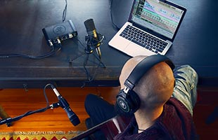 overhead view of musician wearing headphones sitting in front of window with components of Mackie Producer Bundle arranged on dresser in front of him