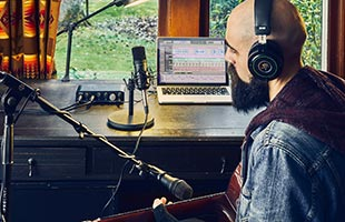 view from behind of musician wearing headphones sitting in front of window with components of Mackie Producer Bundle arranged on dresser in front of him