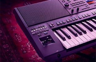detail image of Yamaha PSR-A5000 showing left speaker, pitch bend and modulation joystick, portion of control panel and portion of keybed