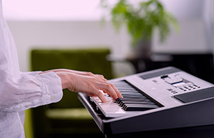 close-up side view of musician playing Yamaha PSR-E373 in living room