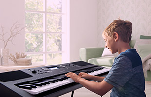 side view of young boy playing Yamaha PSR-E373 in living room