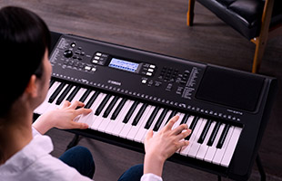 rear over-the-shoulder view of musician playing Yamaha PSR-EW310 in living room