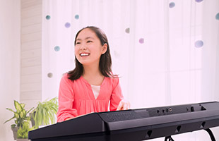 front view of young girl playing Yamaha PSR-E373 in living room