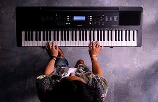 overhead view of musician playing Yamaha PSR-EW310 above stone floor